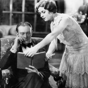 1920s pic of man and woman looking at book