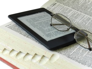 Pair of glasses on a Kindle and a print dictionary