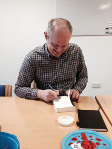Ian Sutherland signing a book