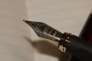 Fountain pen nib poised over blank page