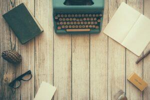 Image of typewriter, pen, glasses, etc