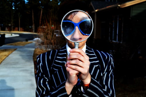 Photo Of Person Looking Through Magnifying Glass