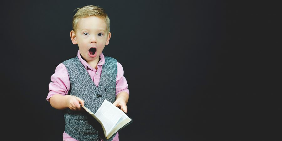 Picture Of Small Boy Startled At What He Has Just Read In A Book