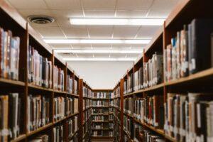 lines of bookshelves full of books in a library