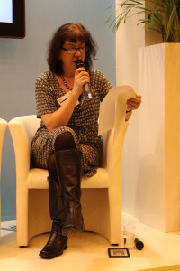 Debbie Young seated, speaking into a microphone, reading from a script