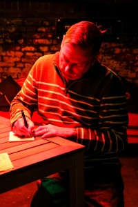 Photo of Chris Casburn signing a book