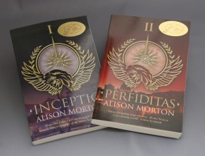 Image of two of Alison Morton's books with the gold sticker on the cover indicating they've passed INDIE B.R.A.G.'s quality control