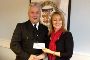 Sandy donates a percentage of her profit to the Police Dependants' Trust  - pictured here presenting a donation to District Commander Geoff Spicer.