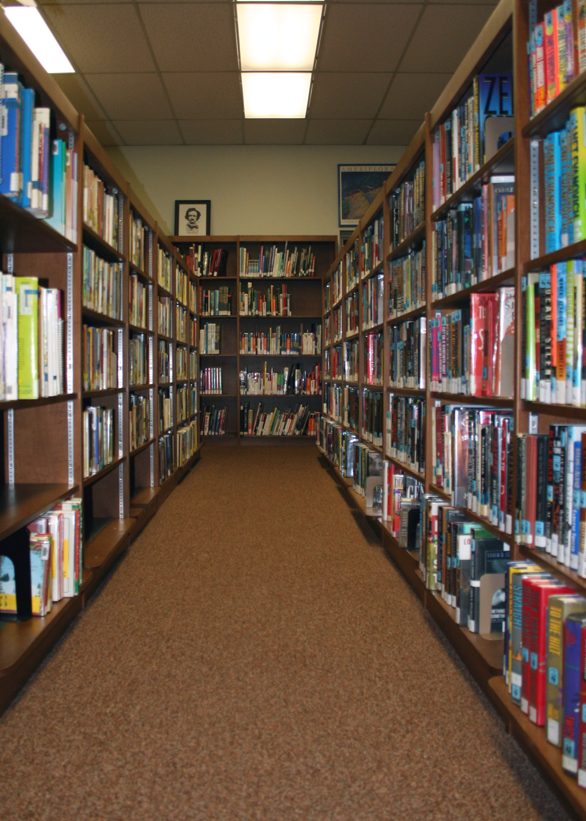 Photo Looking Down A Row Of Shelves In A Library