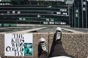 View from top of a high building with a book next to a pair of feet