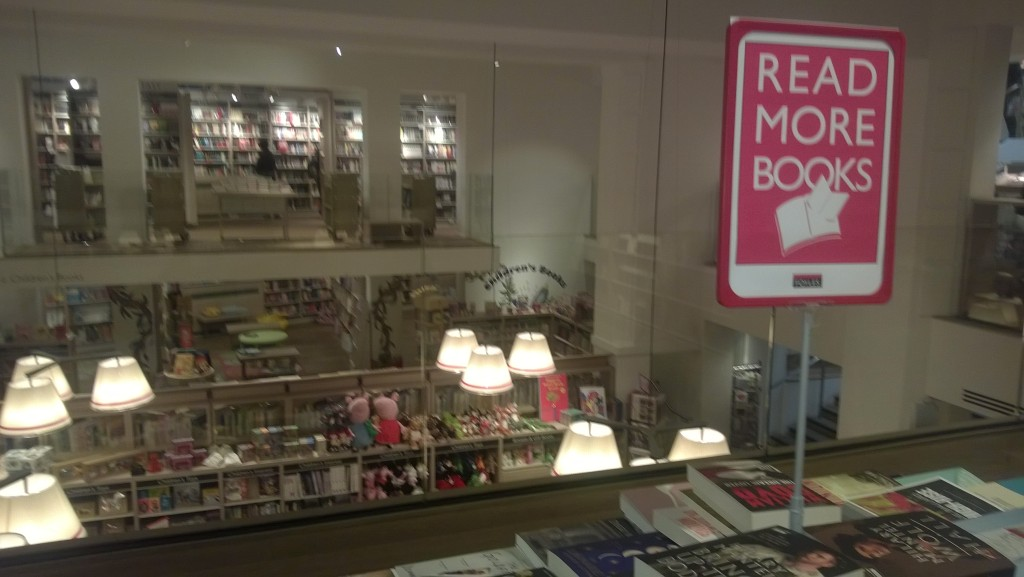 "Inside bookshop with sign saying ""Read More Books"""