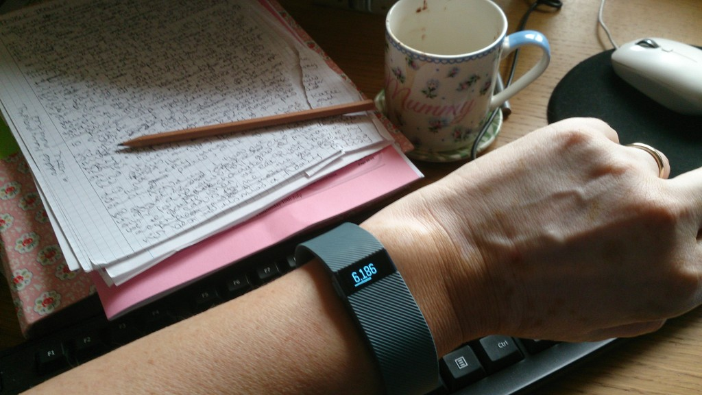 photo of wrist at desk showing Fitbit with paces below daily target
