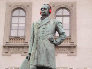 Old statue wearing audio headphones