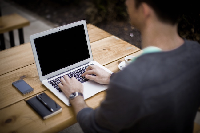 Photo of person typing into laptop