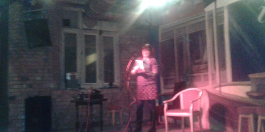 Hazy Photo Of Author Reading On Stage