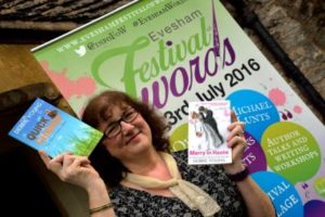 Debbie Young holding up two books in front of a festival banner