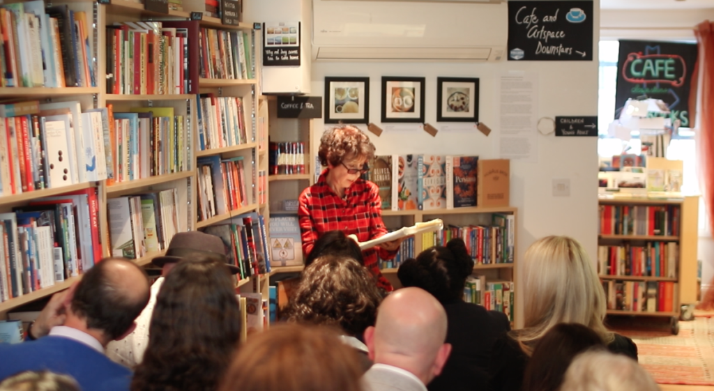 Photo of an author reading to a group in a bookshop