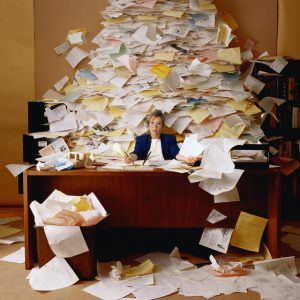 Woman at desk with huge pile of paper behind her desk
