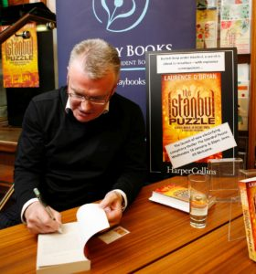 Photo of Laurence O'Bryan signing a book