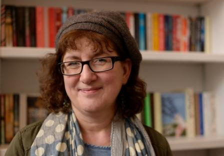 Headshot Of Debbie Young In Front Of Bookshelves