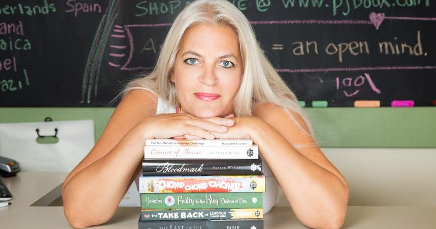 Headshot Of Patti With A Pile Of Books