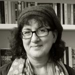 Headshot of Debbie Young in front of bookshelf