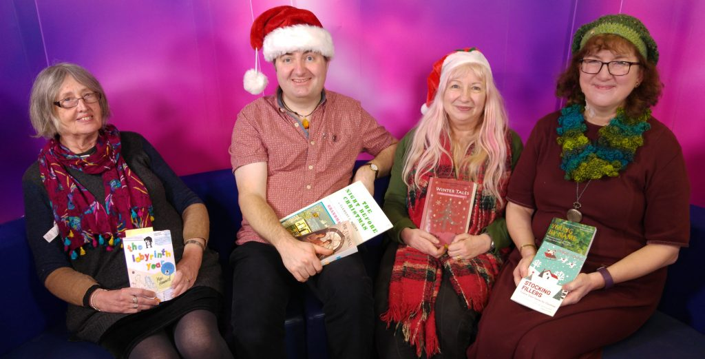 Four authors in Christmassy clothes with their festive books