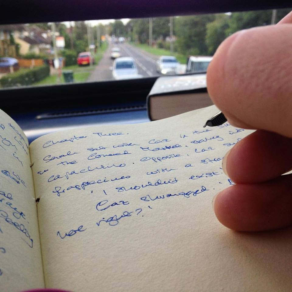 photo of author's hand writing in his notebook on the bus