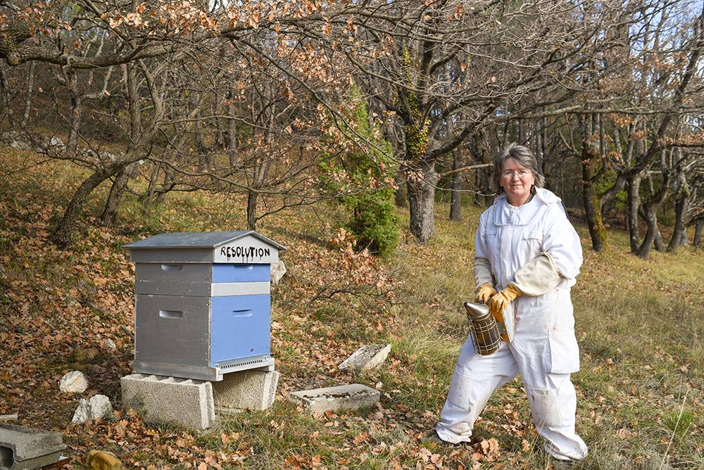 Photo of Jean Gill tending to her beehive