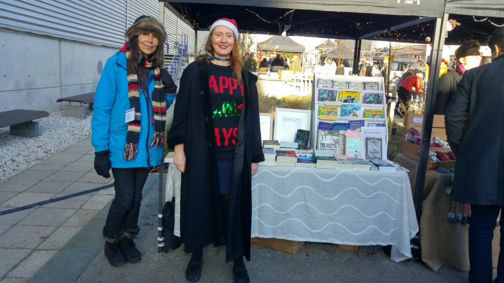 Ana and Helen in winter coats by the stall