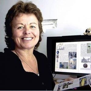 headshot of Sally with book and computer