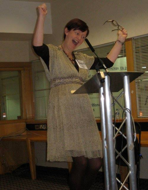 Photo Of Orna At A Lectern Waving Arms Enthusiastically