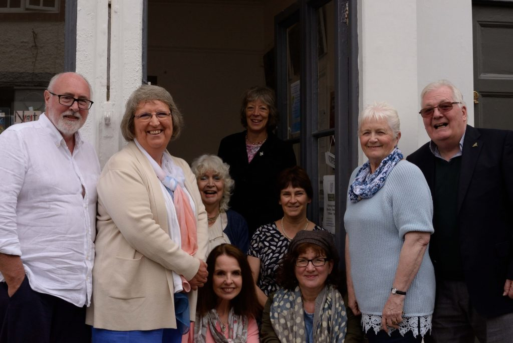 group shot of authors and proprietor on doorstep