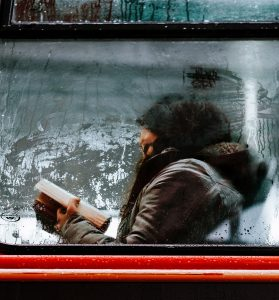 girl reading book on bus