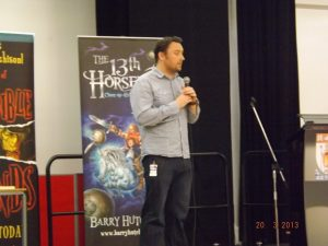 Photo of Barry with a microphone giving a talk