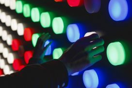 photo by Katya Austin on Unsplash of hands on different coloured lights looking like an experiment