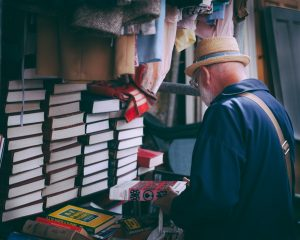 old man browsing pile of books whose spines and covers are concealed