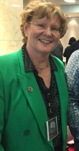 Alison Morton in bright green author uniform jacket
