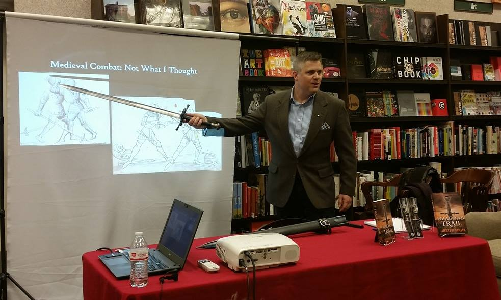 Photo of Joe Malik pointing at a screen with the tip of his sword