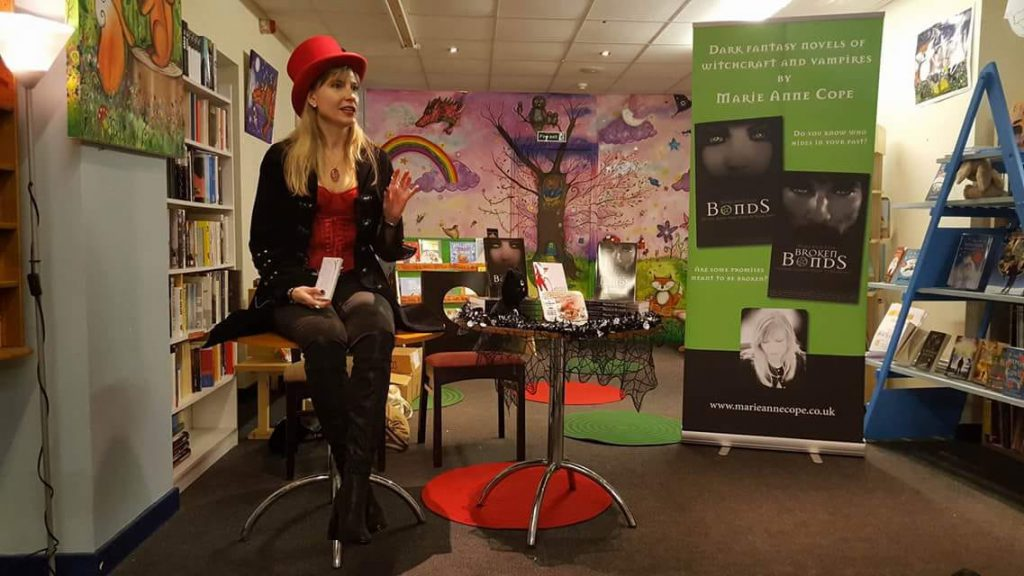 Marie Cope sitting on a stool in black and red with top hat