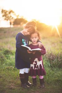two children read a book