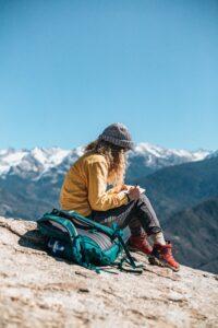girl sitting writing on mountain