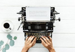 photo of hands on a typewriter keyboard