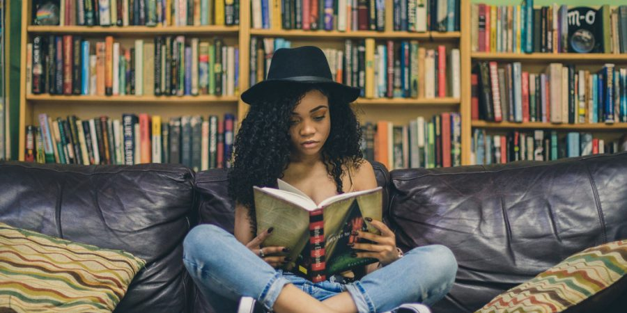 Photo Of Girl Sitting On Sofa Reading Book In Front Of Extensive Bookshelves To Illustrate What Makes Readers Buy Books