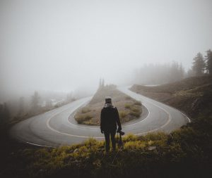 photo of u-bend in road and man looking at it to signify a turning point (image by Vladislav Babienko via unsplash.com)