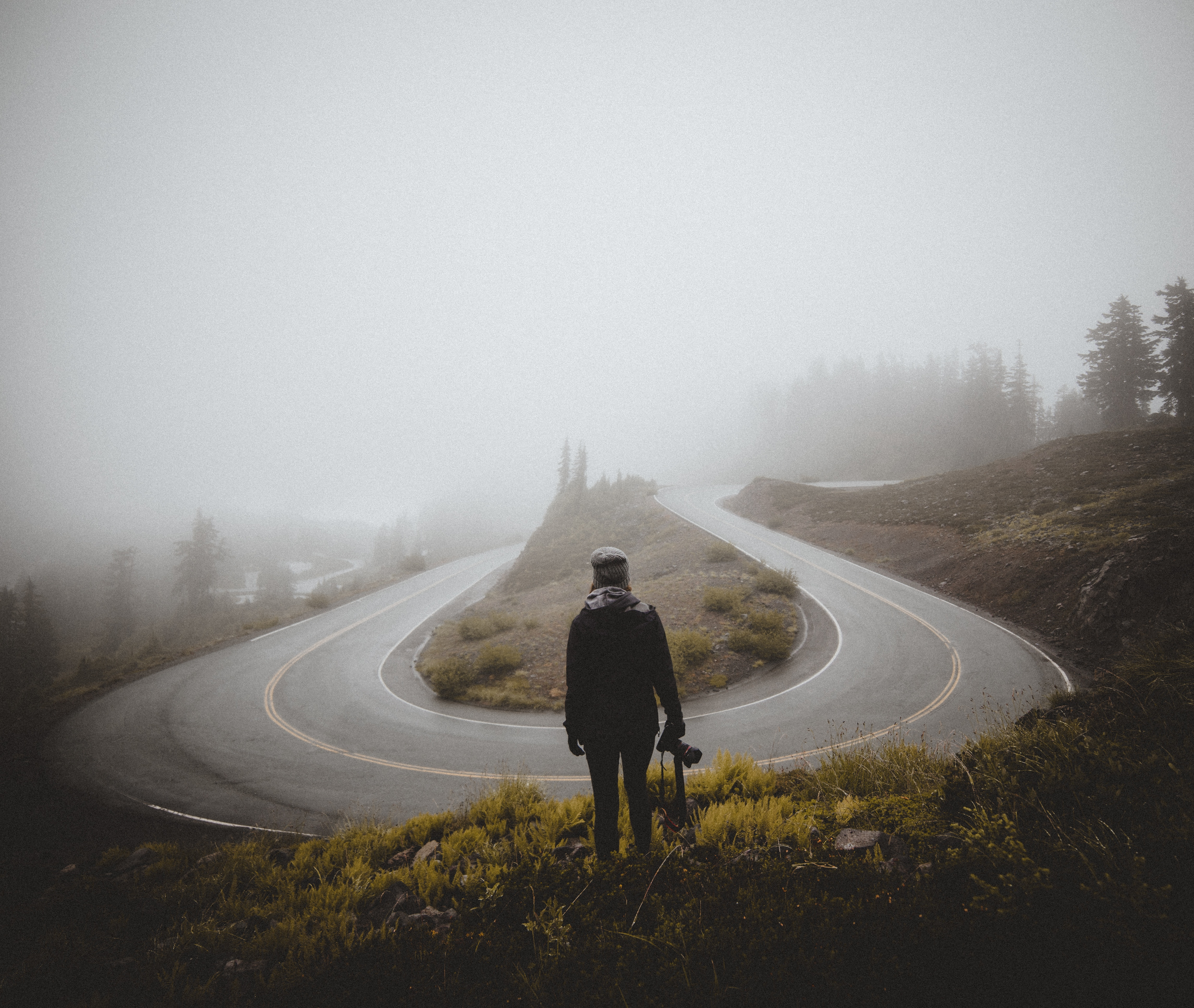 Photo Of U-bend In Road And Man Looking At It To Signify A Turning Point