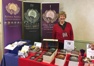 Alison Morton at an exhibition stand with her fiction of different lengths