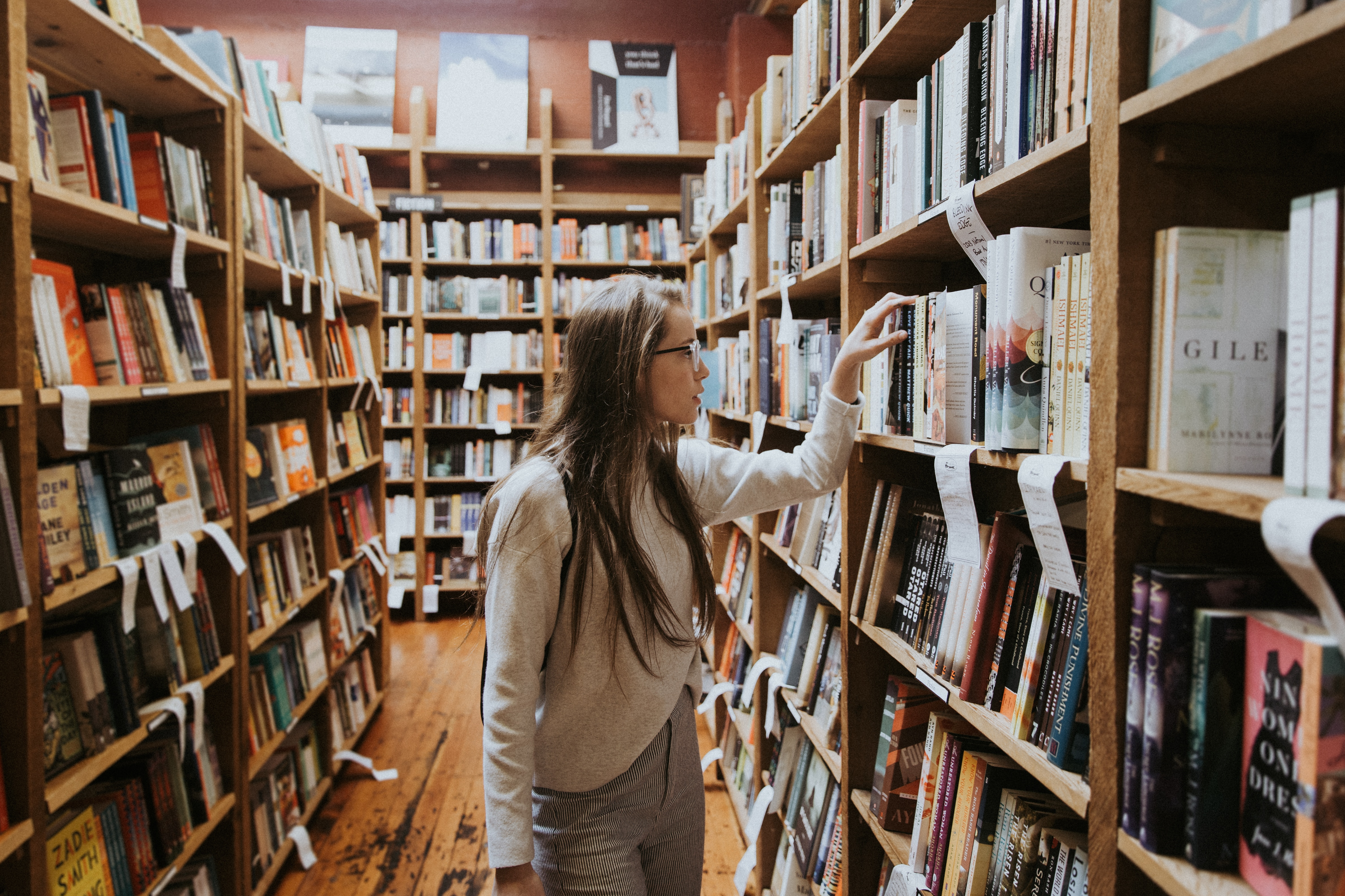 A Woman Browsing Shelves In A Bookstore