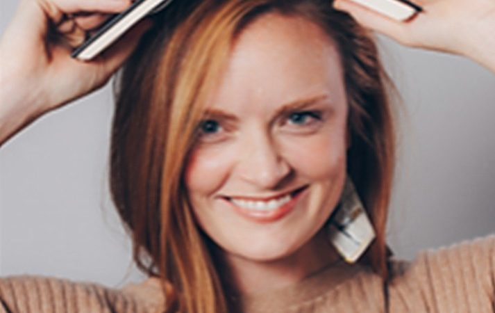 Headshot Of Meghan Harvey With Book On Her Head