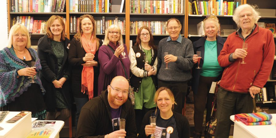 Photo Of Them With Glass Of Bubbly In Front Of Bookshelves